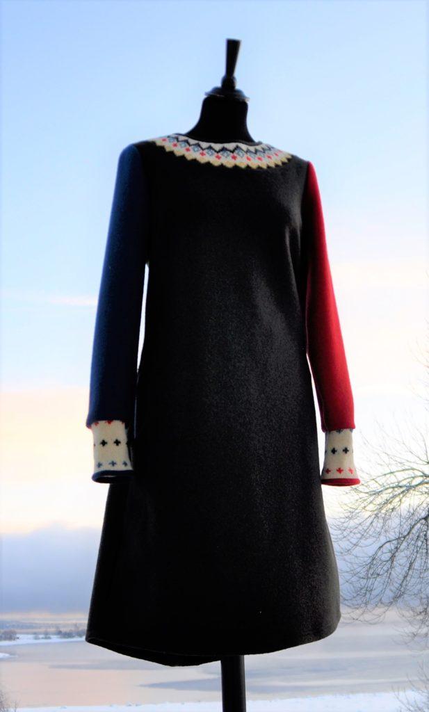 11 Olivenfarget kjole med en dus rød og en dus blå erm og rester fra en gamme strikkekofte i halsen,