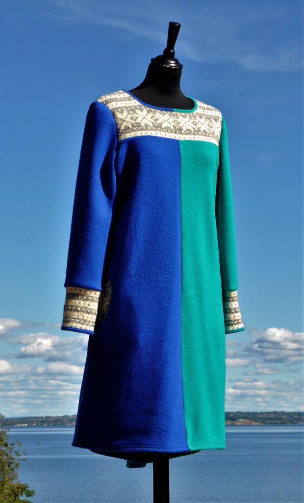 Kjole med en turisgrønn og en kongeblå side, lommer og med Fanakofte. Str M/L, Kr. 2900